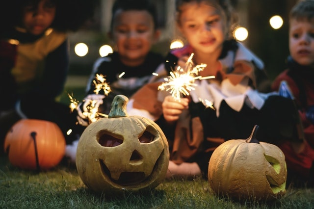 Children with sparklers & carved pumpkins